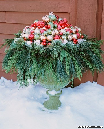 outdoor christmas urn filled with glass ball ornaments and ever green branches